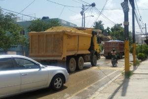 """Residentes en """"El Edén"""" de Villa Mella se quejan porque vehículos pesados dañan sus calles y llenan de polvos las viviendas"""